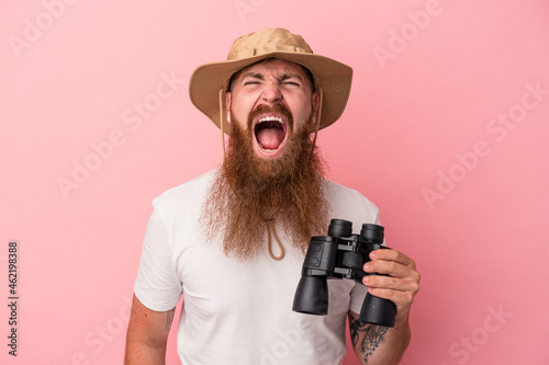 Vászonkép Young caucasian ginger man with long beard holding binoculars isolated on pink background screaming very angry and aggressive