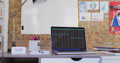 Laptop with data processing standing on desk in office