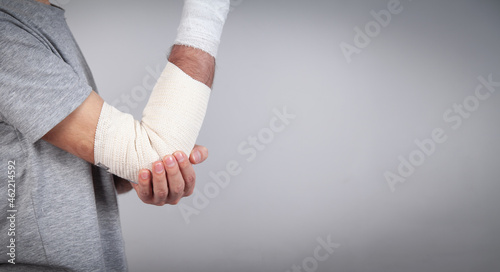 Foto Man hand with elastic bandage on elbow.