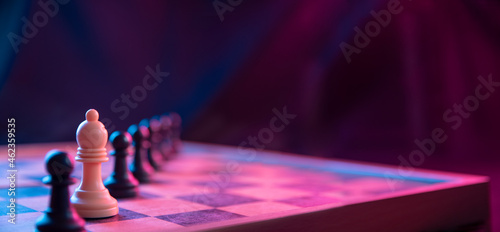 Fotografering Chess pieces on a chessboard on a dark background shot in neon pink-blue colors