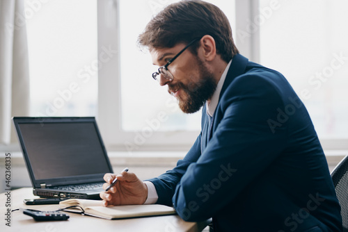 Murais de parede bearded man sitting at a desk in front of a laptop stress anger professional