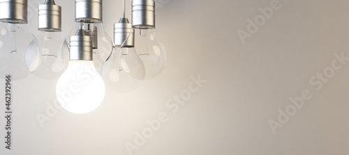 Tableau sur Toile Glowing lightbulb on blurry panoramic concrete wall background