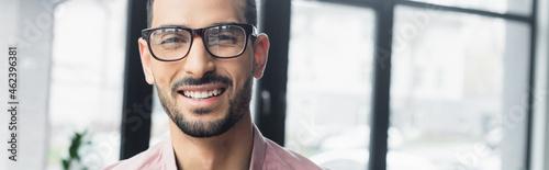 Photo Cheerful muslim businessman in eyeglasses looking at camera in office, banner