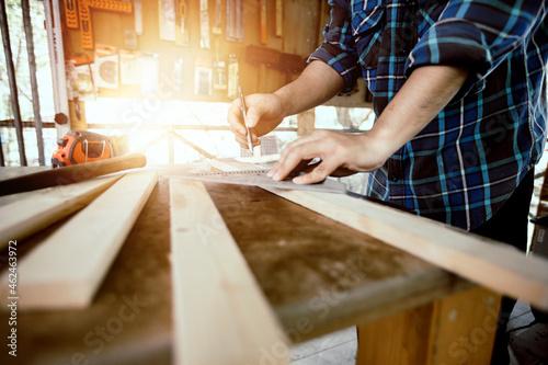 Wallpaper Mural close up carpenter man working and measure wood in shop