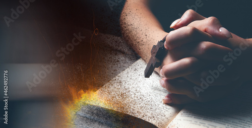 Fotografie, Obraz a woman praying on a book while the book is burning