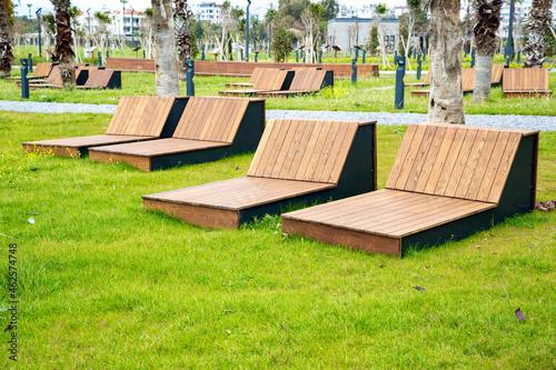 Obraz na plátně Wooden sun loungers placed on grass in a park in Mersin, Turkey.