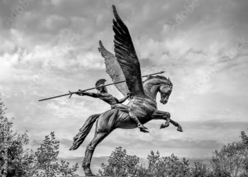 Wallpaper Mural Bellerophon riding winged horse pegasus spear in hand dark sky moody, trees blac