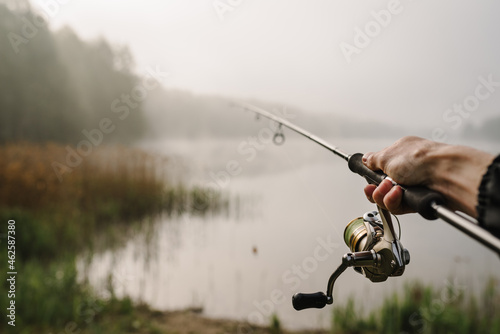 Photo Fisherman with rod, spinning reel on river bank