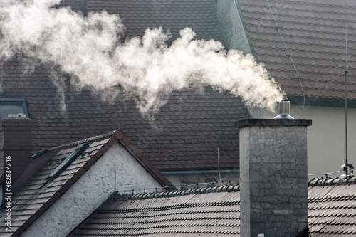 Smoke rising from the chimney in city Fototapet