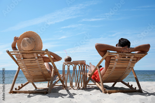 Tablou Canvas Couple resting in wooden sunbeds on tropical beach