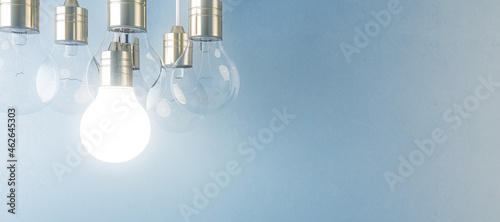 Canvas Glowing light bulb on blurry wide blue wall background