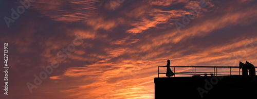 Fotografie, Obraz Woman on  deck of a a vintage old ocean liner watching the beautiful sky over the ocean