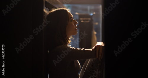 Fotografie, Tablou Loneliness Asian woman sitting on the floor with hugging herself