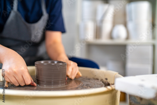 Fotografija Asian woman sculptor artist hands sculpture clay on pottery wheel at ceramic studio