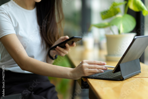Female working on portable digital tablet and smart mobile phone in co-working space