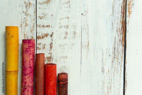 Fotomural Shot of colorful bamboos on a white plank background