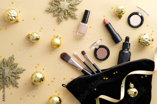 Makeup bag with cosmetic products and golden Christmas decorations spilling out on to pastel beige background Fototapet