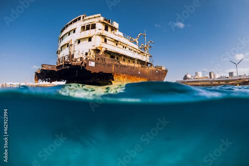 Fotografie, Obraz Split shot in blue ocean with wreck ship. Arrecife, Lanzarote