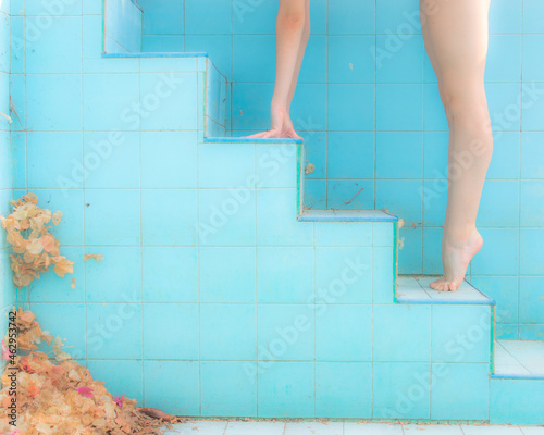 Fotografia Arm and leg of woman in a ballerina tiptoe position, ascending on a pool steps