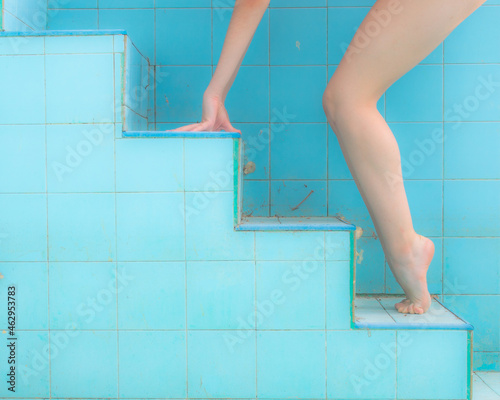 Murais de parede Leg and hand of woman in a ballerina tiptoe position, ascending on a pool steps