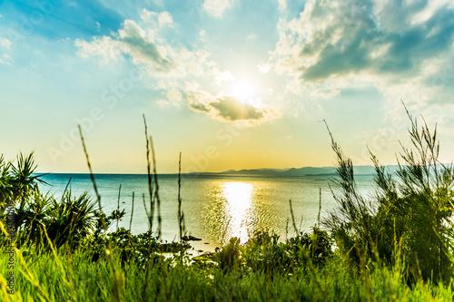 Fototapeta 海の上で雲に隠れる太陽。沖縄県小浜島