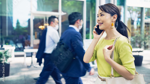 街を歩きながらスマホで通話する女性