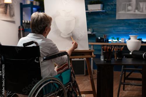 Fotografie, Obraz Invalid aged artist drawing vase on canvas using pencil in artwork studio