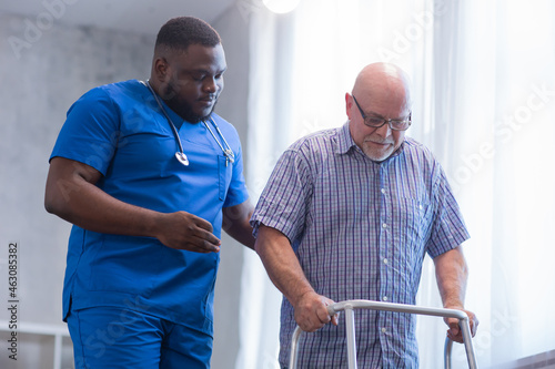 Caregiver is teaching old man to walk with walker. Professional nurse and patient in a nursing home. Assistance, rehabilitation and health.