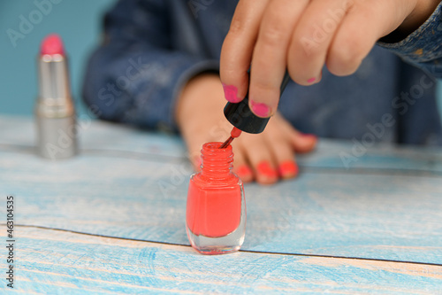 A girl painted with her mother's makeup dips a brush into a bottle of nail polish Fototapeta