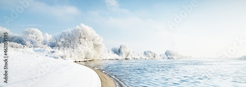 Valokuva Snow-covered trees in a city park, a view of the embankment and river