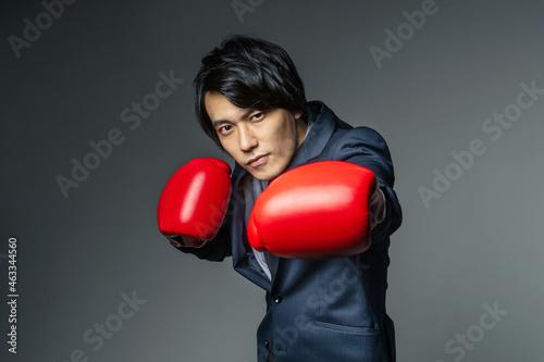 ボクシンググローブをつけてパンチをするビジネスマン