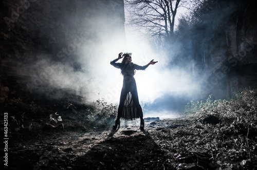 Fotografia A young witch dances and conjures on Halloween night in smoke and light at the festival of the dead