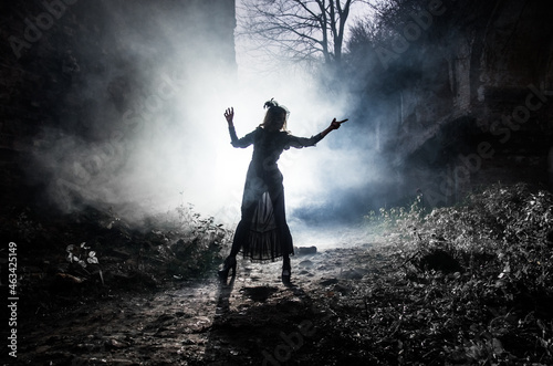 Obraz na płótnie A young witch dances and conjures on Halloween night in smoke and light at the festival of the dead