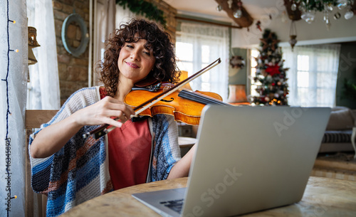 Woman music teacher teaching how to play a song the violin online during a video call