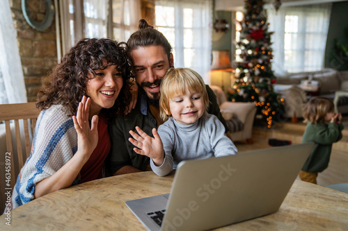 Happy family with kid having fun using laptop together, watching internet video, making online call