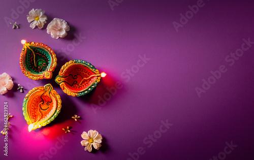 Happy Diwali - Clay Diya lamps lit during Dipavali, Hindu festival of lights celebration. Colorful traditional oil lamp diya on purple background