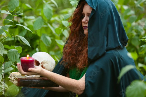 Obraz na plátně Young witch with skull, candle and spell book in green forest
