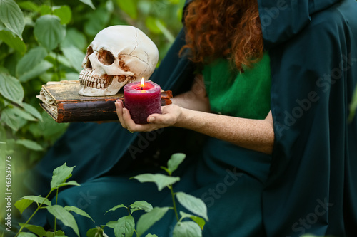 Fotografie, Obraz Young witch with skull, candle and spell book in green forest