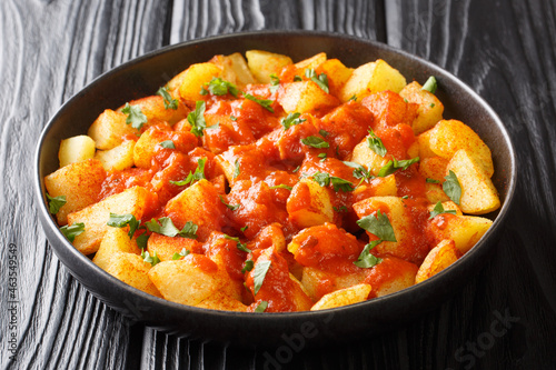 Patatas bravas or potatoes in bravas sauce are a classic Spanish tapas dish close up in the plate on the table Fototapet