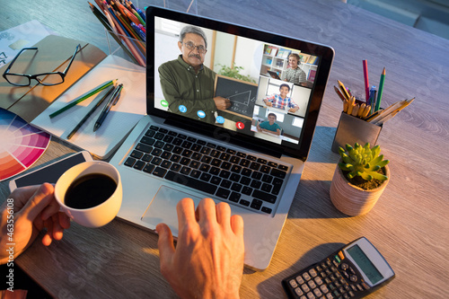 Hands of man using laptop for video call, with smiling diverse elementary school pupils on screen