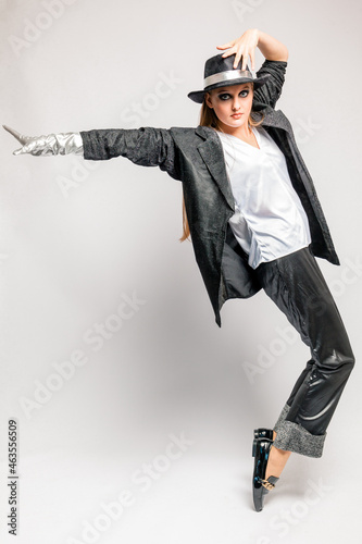 Wallpaper Mural A young pretty teenage girl in a man's black suit and hat dances in the studio o