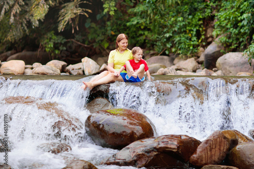 Family with child at waterfall. Travel with kids.
