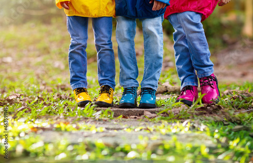 Colorful kids shoes. Children play outdoor.