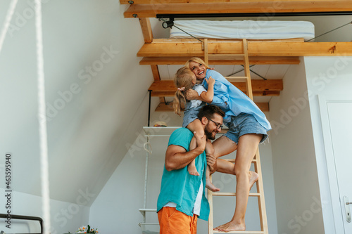 Mother is standing on the ladder and hugging her daughter who is sitting on father shoulders