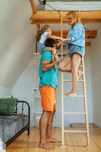 Woman standing on ladder at home and holding hands of daughter who is sitting on father's shoulders