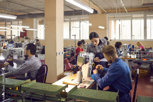 People working in a big workshop room at a shoe factory. Male and female workers sitting at tables with industrial sewing machines and making new footwear details. Manufacturing industry concept