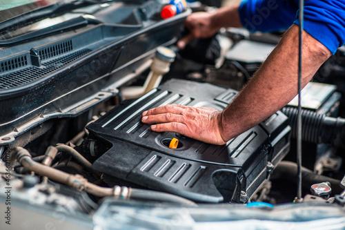 Obraz na plátně Laborer concept, a very experienced car technician is inspecting the car engine