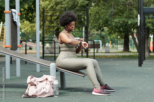 Plus size sportswoman in tracksuit looking at wristwatch while sitting on sports facilities