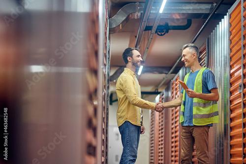 Fototapeta Two men shaking hands near warehouse garages