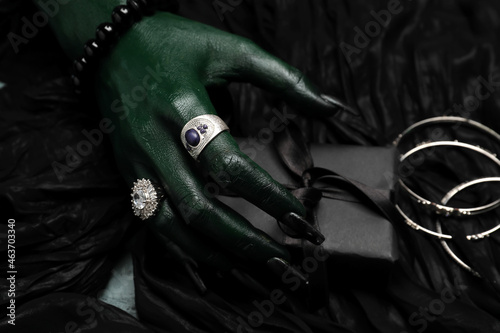 Fototapeta Hand of witch with gift box on dark background